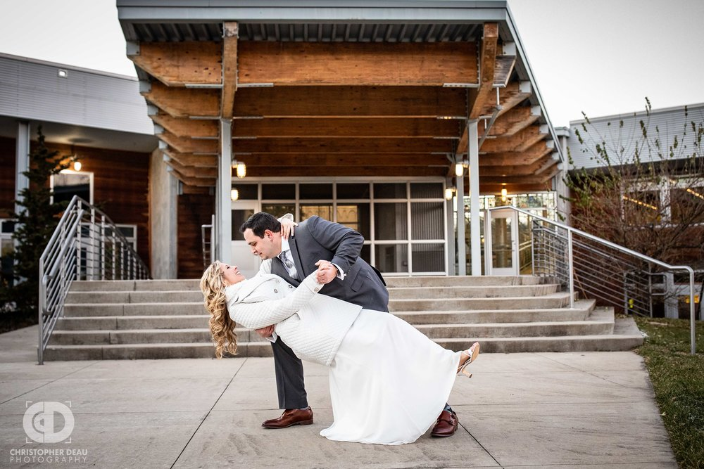 The Groom dips and kisses his bride in front of the Girl Scouts Heart of Michigan Building in Kalamazoo during their wedding reception
