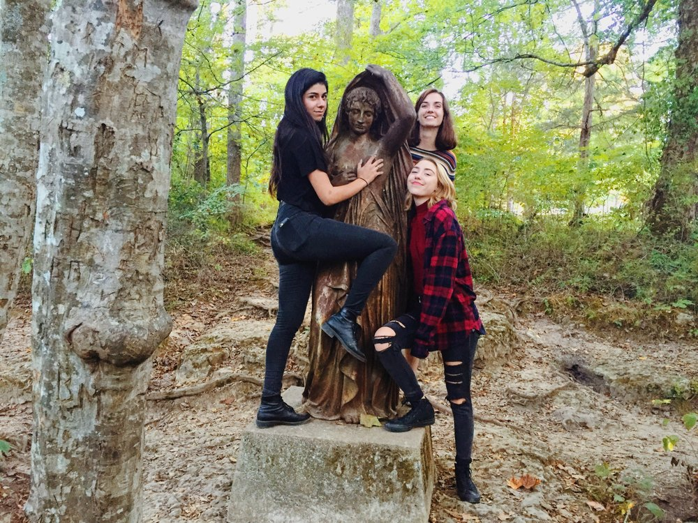A photo of Dilvin, Megan, and Addie not groping a statue.