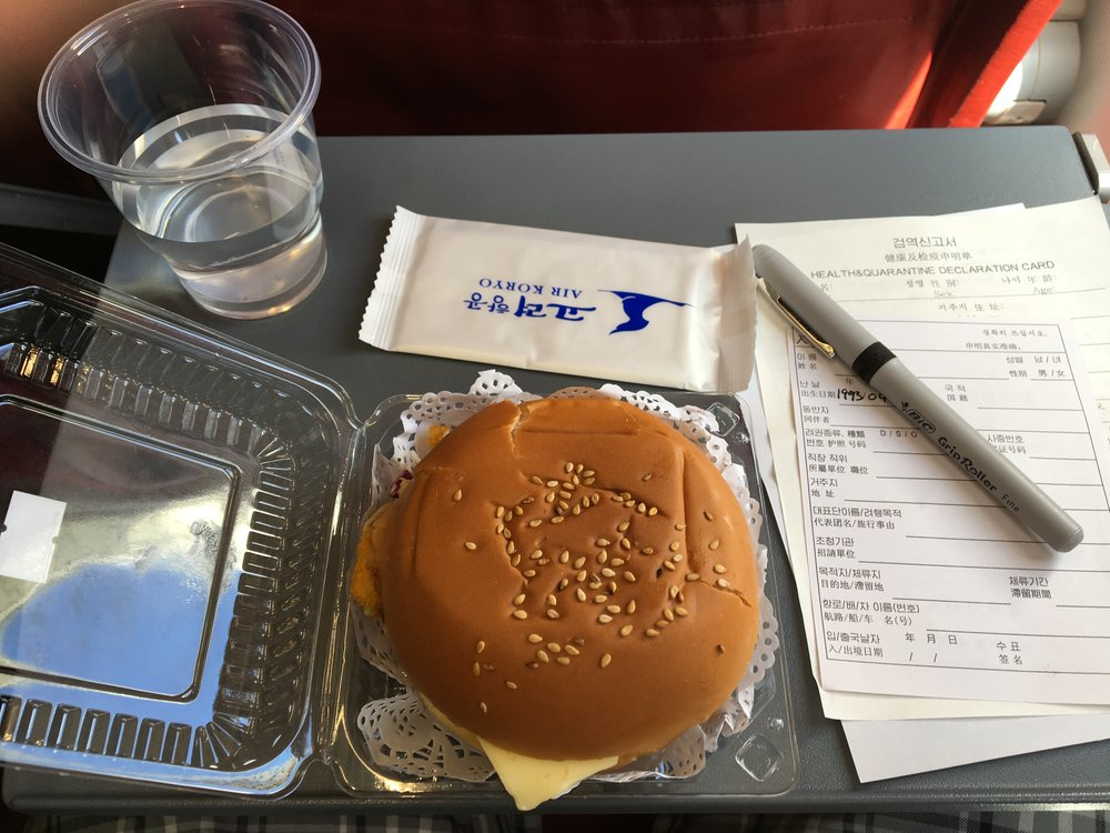 Chicken sandwich lunch and customs forms aboard Air Koryo