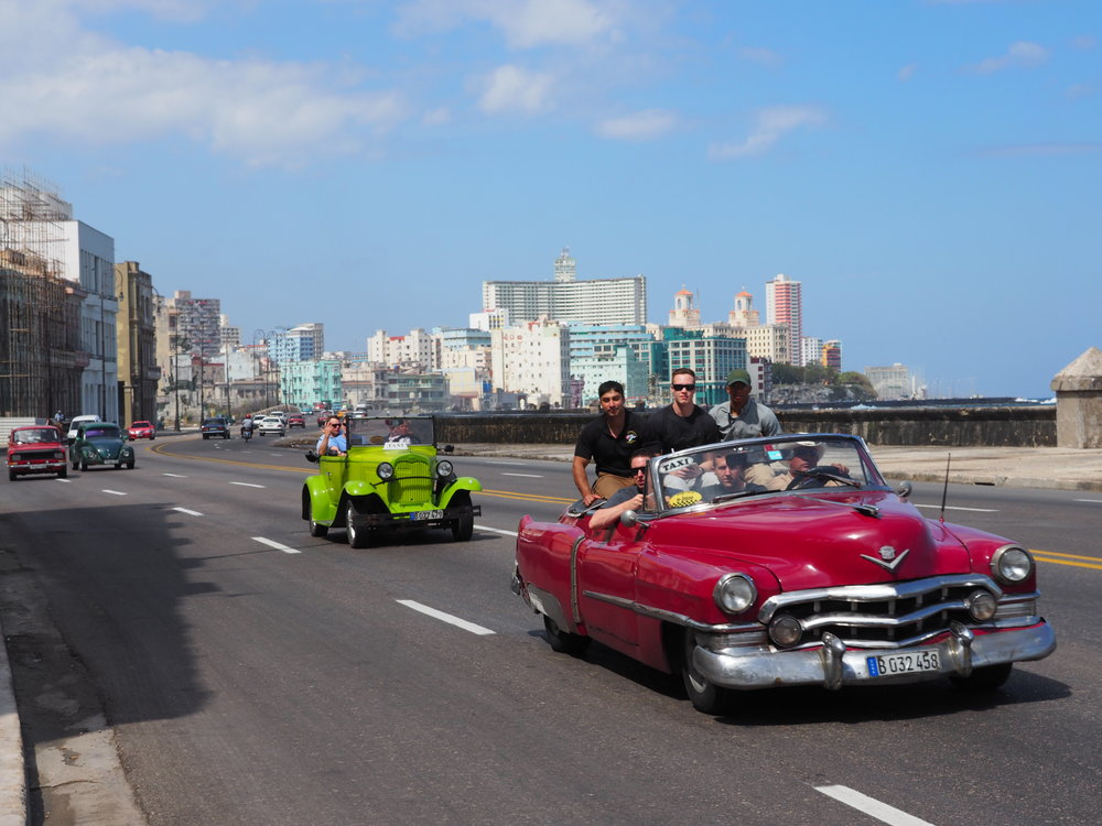 Tourists riding in a classic convertible on the Malecon