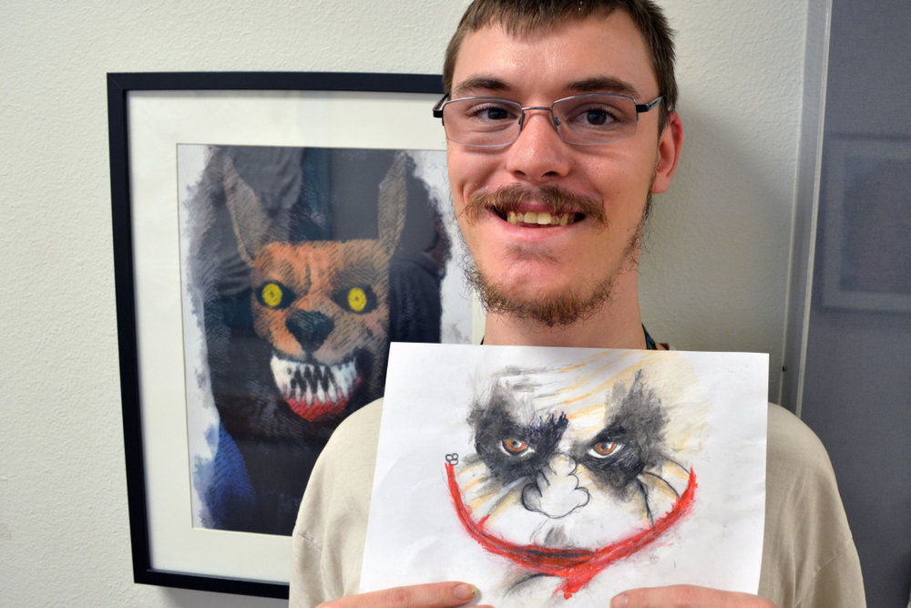 Gabriel with two of his drawings.