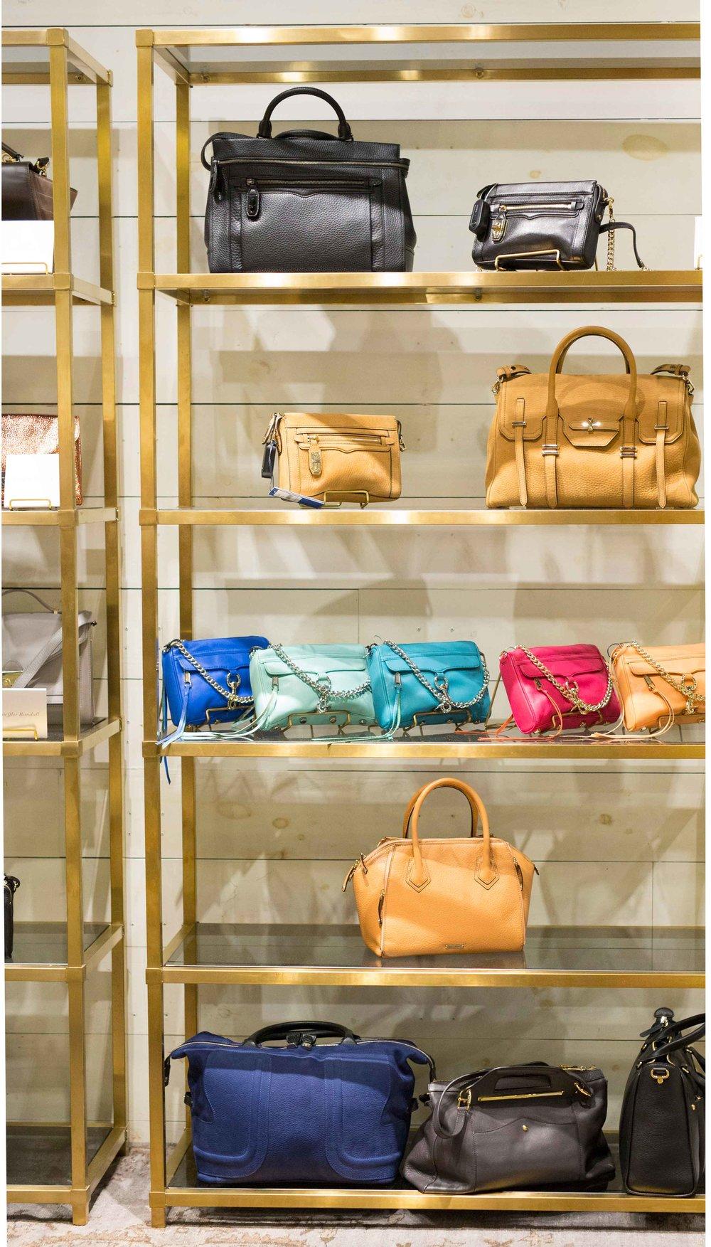 Custom brass bookshelves compliment the clothing racks on the opposite side of the store.