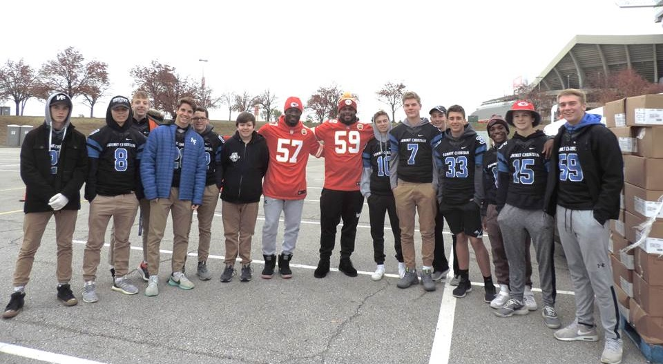 Several members of the SCA Varsity Football team take a break from working to get a picture with Chiefs linebackers Kevin Pierre-Louis and Reggie Ragland