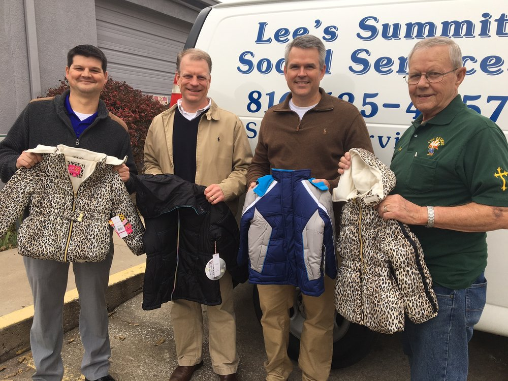 Lee's Summit Social Services executive director Matt Sanning (left) accepted a donation of coats from members of the Lee's Summit Knights of Columbus council.