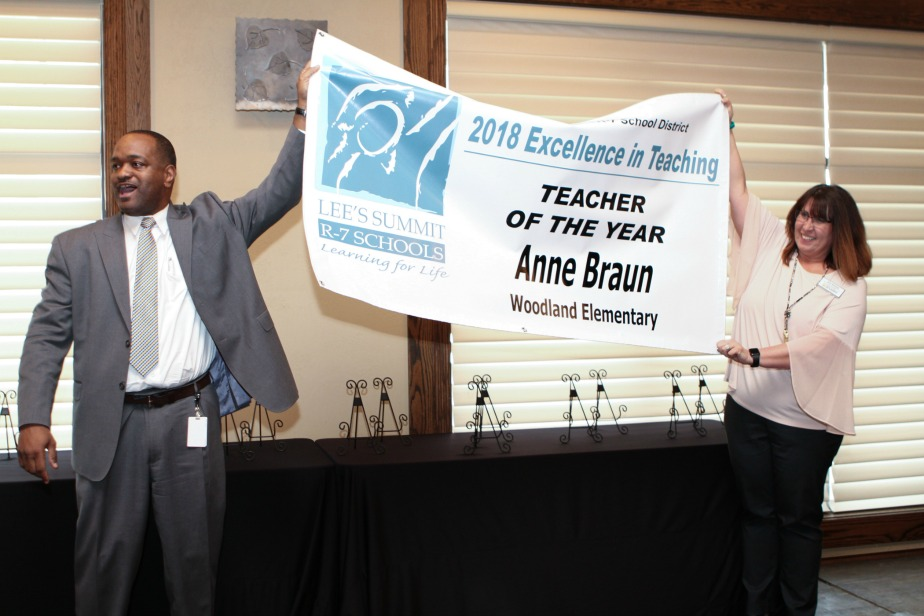 Dr. Dennis L. Carpenter, R-7 superintendent, and Jodi Briggs of the Chamber Education Committee unfurl the banner announcing the Teacher of the Year.