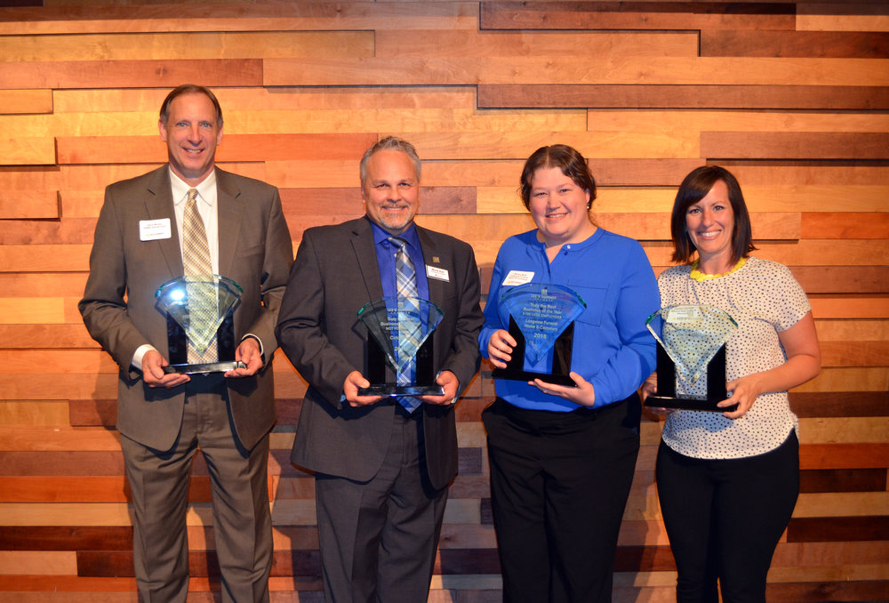 Photo courtesy Lee's Summit Chamber  |  Gene Brixey (HSMC Orizon LLC), Monte Stull (Coldwater), Melissa Beall (Longview Funeral Home & Cemetery) & Candace Jennings (Whistle Stop Coffee & Mercantile) accept the Chamber's 2018 Truly the Best Business of the Year awards.