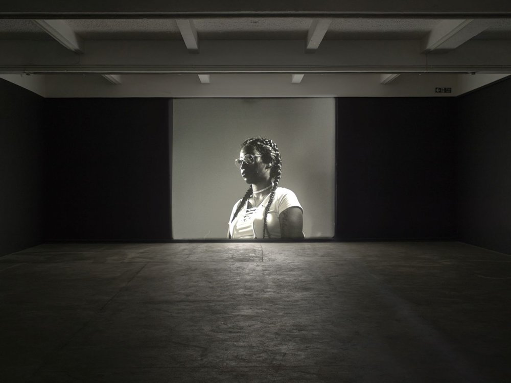 "Luke Willis Thompson,  Autoportrait , 2017, Installation view, Chisenhale Gallery 2017. Photo: Andy Keate  ""Luke Willis Thompson's 35mm film  Autoportrait  is a silent portrait of Diamond Reynolds. In July 2016, Reynolds used Facebook Live to broadcast the moments immediately after the fatal shooting of her partner Philando Castile by a police officer during a traffic-stop in Minnesota, United States. Reynolds' video circulated widely online and amassed over six million views. In November 2016, Thompson established a conversation with Reynolds, and her lawyer, and invited her to work with him on the production of an artwork. Thompson wanted to make an aesthetic response that could act as a 'sister-image' to Reynolds' video broadcast, which would break with the well known image of Reynolds, caught in a moment of violence and distributed within a constant flow of news. In June 2017, Reynolds' original video was played to a jury as evidence. Despite the abundance of visual information, the officer who killed Castile was acquitted of all charges. autoportait continues to reopen a question of the agency of Reynolds' recording within, outside of, and beyond the conditions of predetermined racial power structures."" www.deutscheboersephotographyfoundation.org/en"