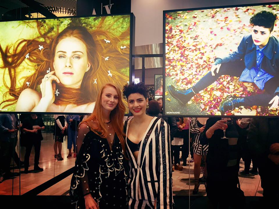 Vera Blue and Montaige stand in front of their portraits. Image via Vera Blue's Facebook page. Top image by Oli Sansom