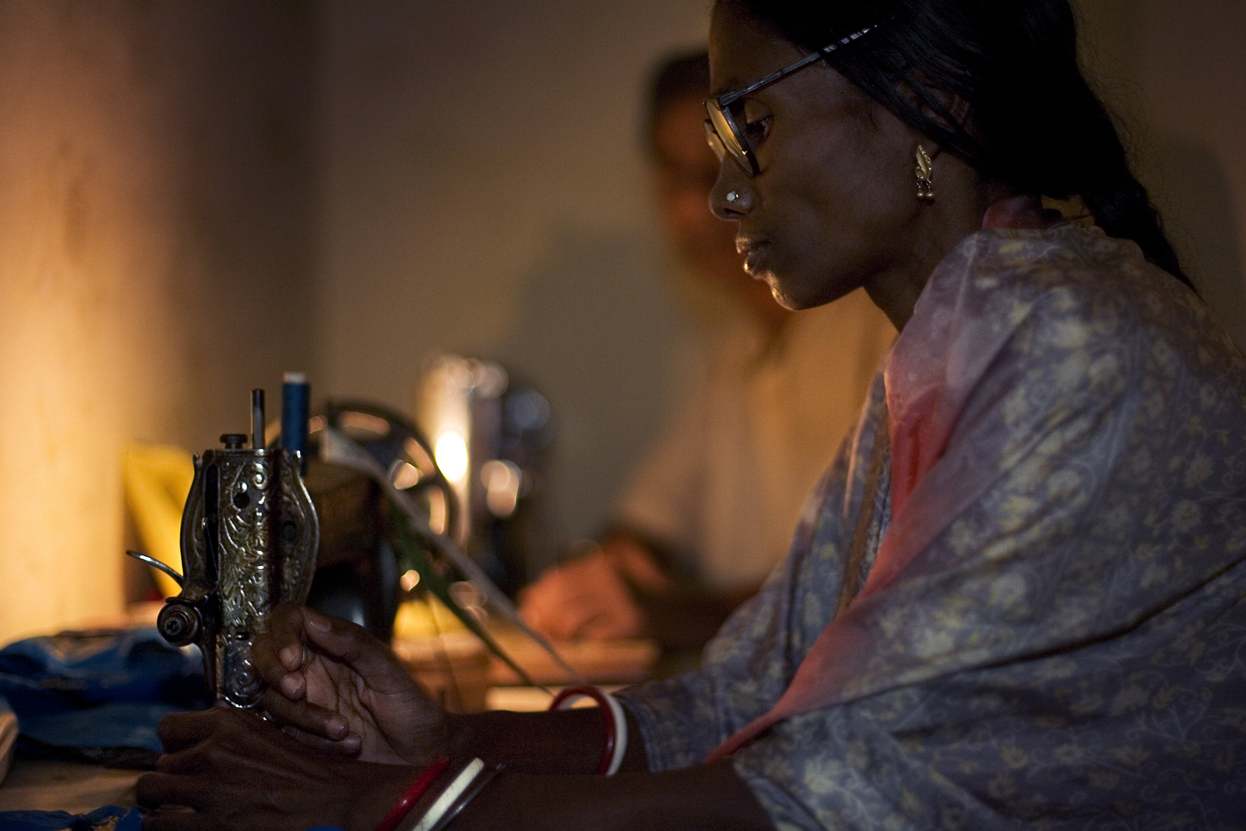 Black woman working by her sewing machine on candlelight, Varana