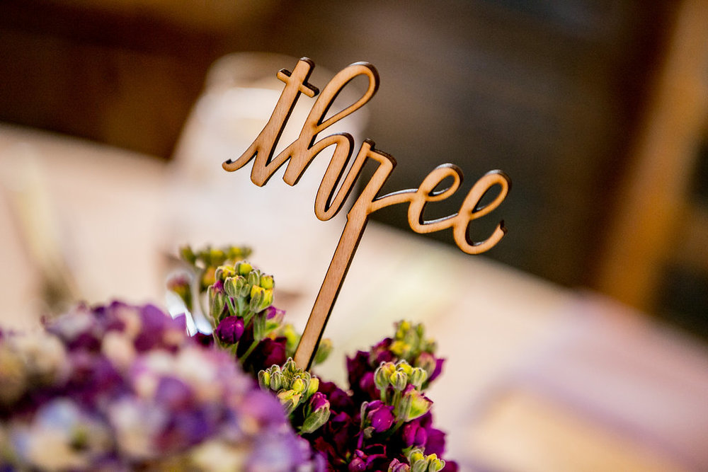 This photo by Brady Puryear features a floral centerpiece by Floral Event Production and a die cut wood table number that saves space on the table.