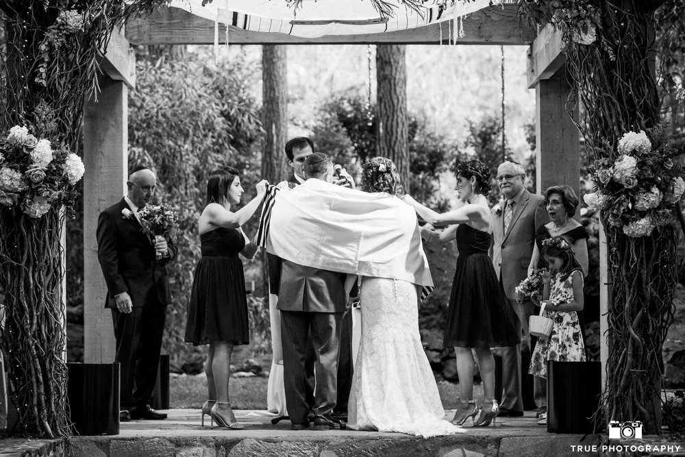 Sisters lovingly drape a tallit over their siblings during this wedding at Calamigos Malibu. Flowers by McCann Florist.  Photo by True Photography.