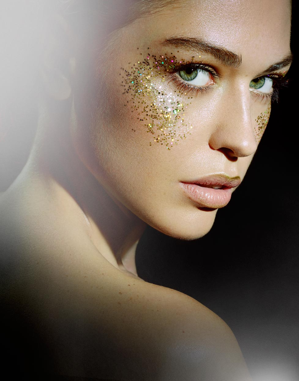 Mark DeLong - Beauty Photographer - Woman with glitter highlights on her cheek looking over her shoulder. Green eyes