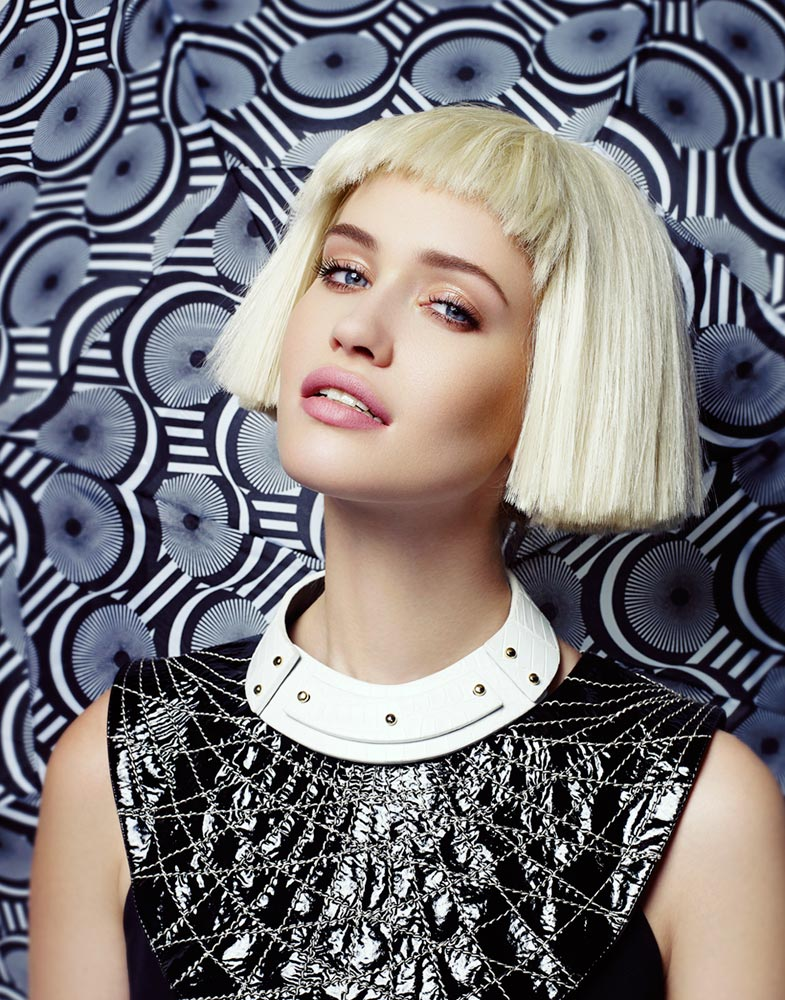 Blond woman with short bangs wearing black leather sleeveless top and white necklace portrait in front of printed backdrop - Mark DeLong: Fashion Gallery