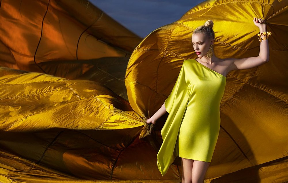 Woman with natural blond hair wearing bright yellow silk dress and red lipstick holding a golden large parachute behind her - Mark DeLong: Fashion Gallery
