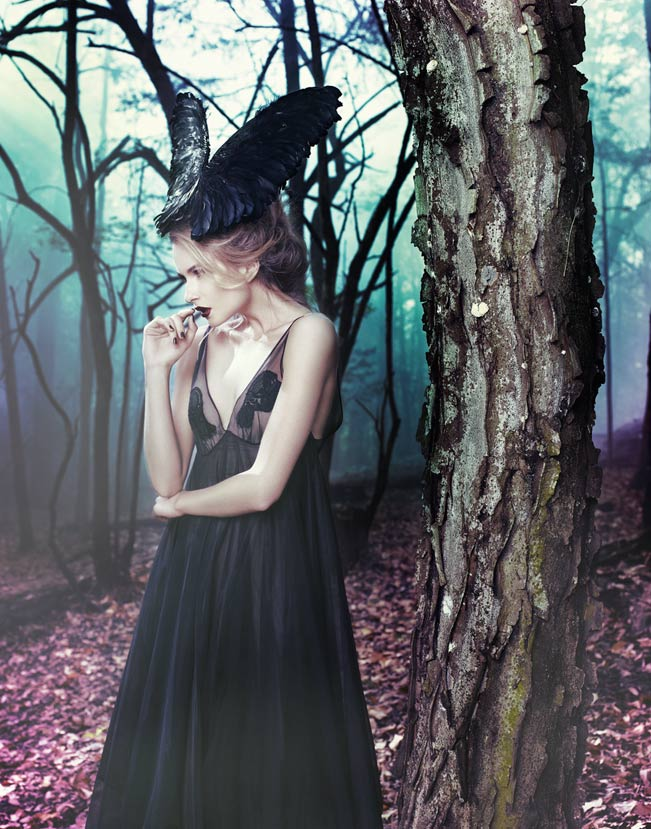 Woman wearing black dress and large black head piece standing in dead forest by tree and purple leaves - Mark DeLong: Fashion Gallery