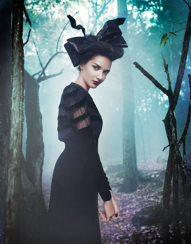 Brunette woman wearing long black dress and black head piece standing in the forest - Mark DeLong: Fashion Gallery