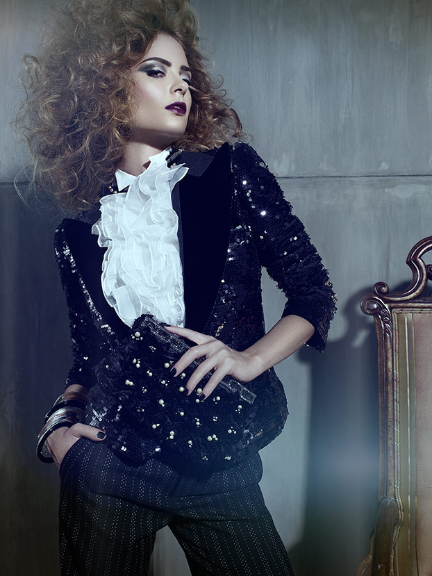 Woman with curly hair posing wearing dark jacket and small matching purse - Mark DeLong: Fashion Gallery