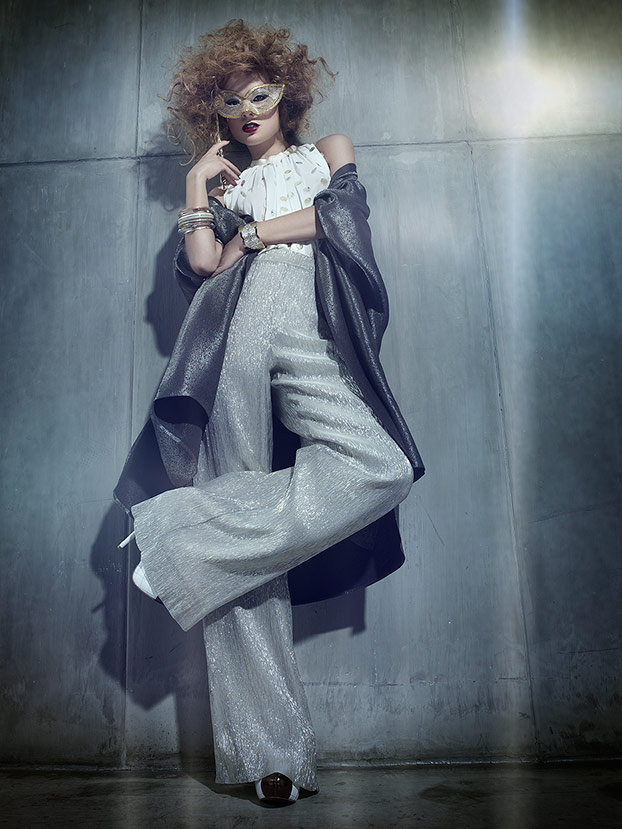 Woman with curly hair wearing white top, gray bell bottom pants and mysterious mask - Mark DeLong: Fashion Gallery