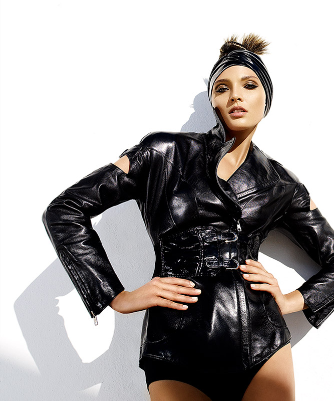 Woman wearing black leather one piece outfit with black headband standing with hands on her hips - Mark DeLong: Fashion Gallery