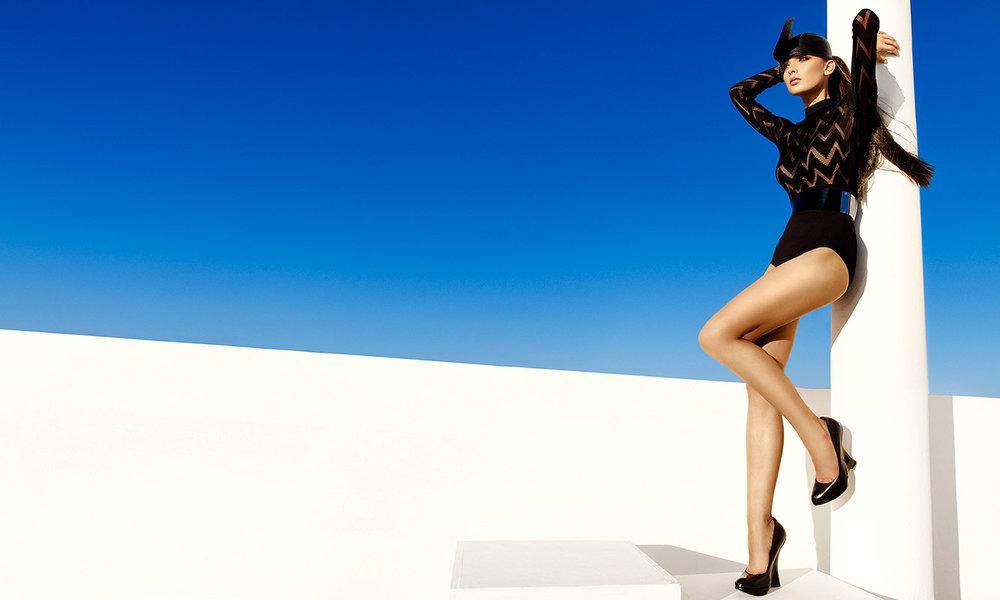Brunette woman wearing black one piece zig zag design jumpsuit leaning against white pole - Mark DeLong: Fashion Gallery