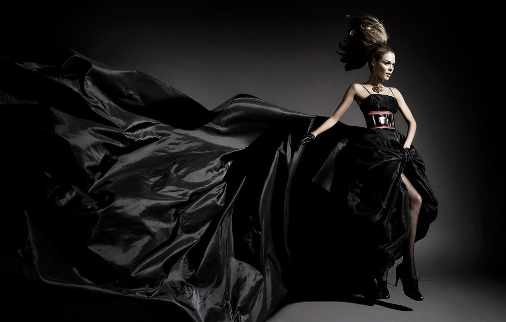 Brunette woman with large black dress flowing behind her walking in a dark background - Mark DeLong: Fashion Gallery
