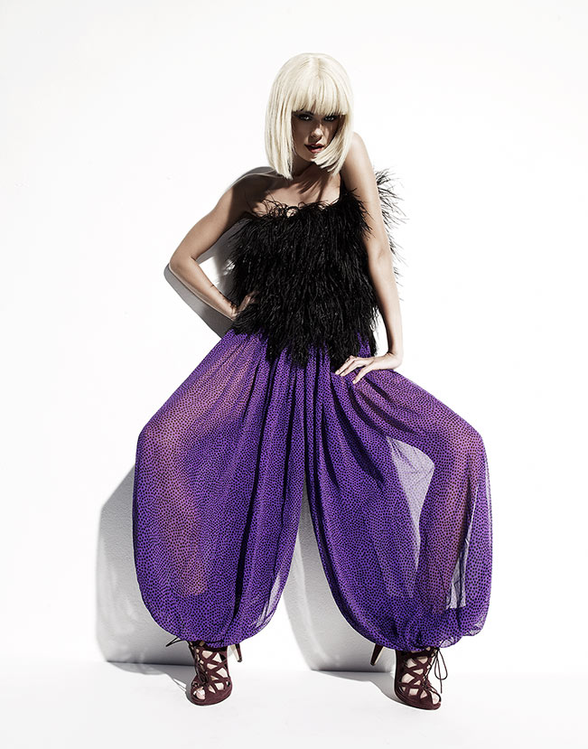 Blond woman with black soft fur top and see through purple pants crouching in front of white backdrop - Mark DeLong: Fashion Gallery