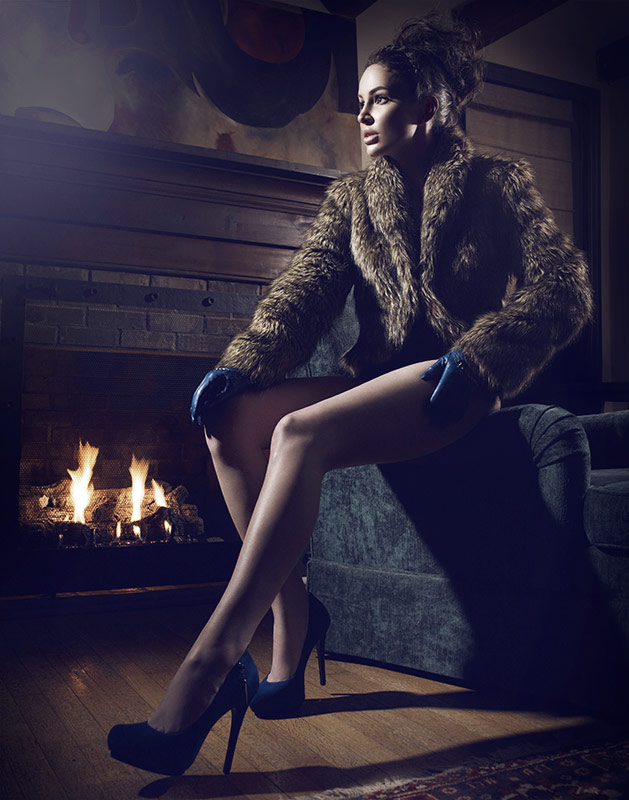 Brunette woman in only brown fur coat sitting by fireplace - Mark DeLong: Fashion Gallery