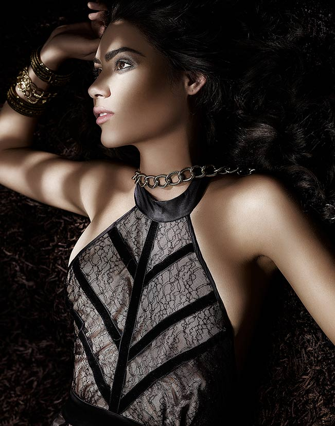 Model with dark hair laying on back with printed symmetrical designed top - Mark DeLong: Fashion Gallery