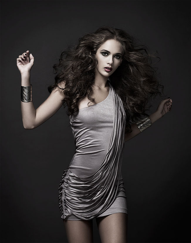 Brunette woman wearing silver short silky dress standing - Mark DeLong: Fashion Gallery