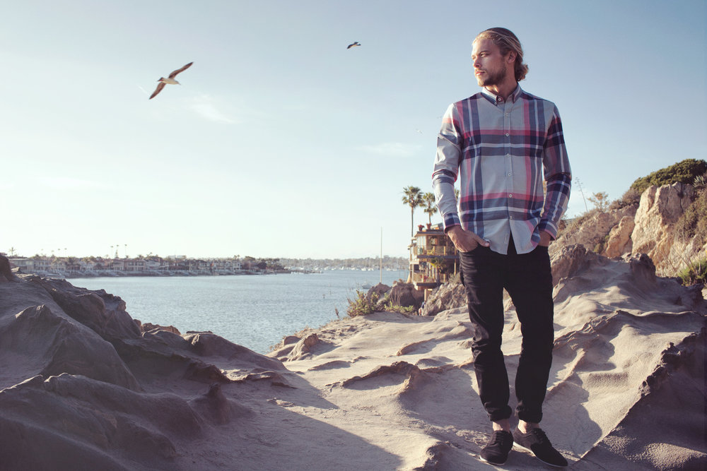 Mark DeLong - Lifestyle Photography - Man standing in the sand on the beach wearing a plaid shirt