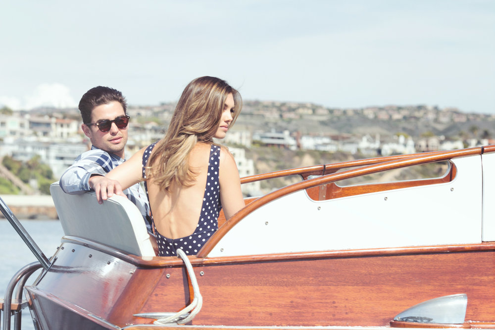 Mark DeLong - Lifestyle Photography - Man with his arm around woman in a blue and white bathing suit sitting on a cris craft boat