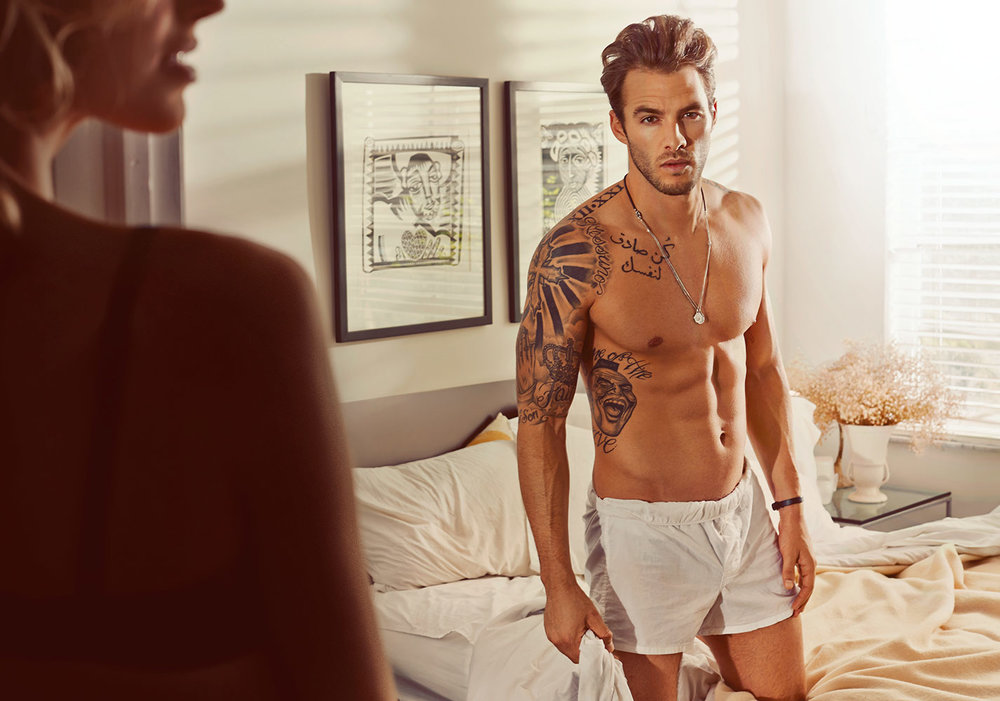Mark DeLong - Lifestyle Photography - Man sitting on a bed in white boxers with a woman in the foreground