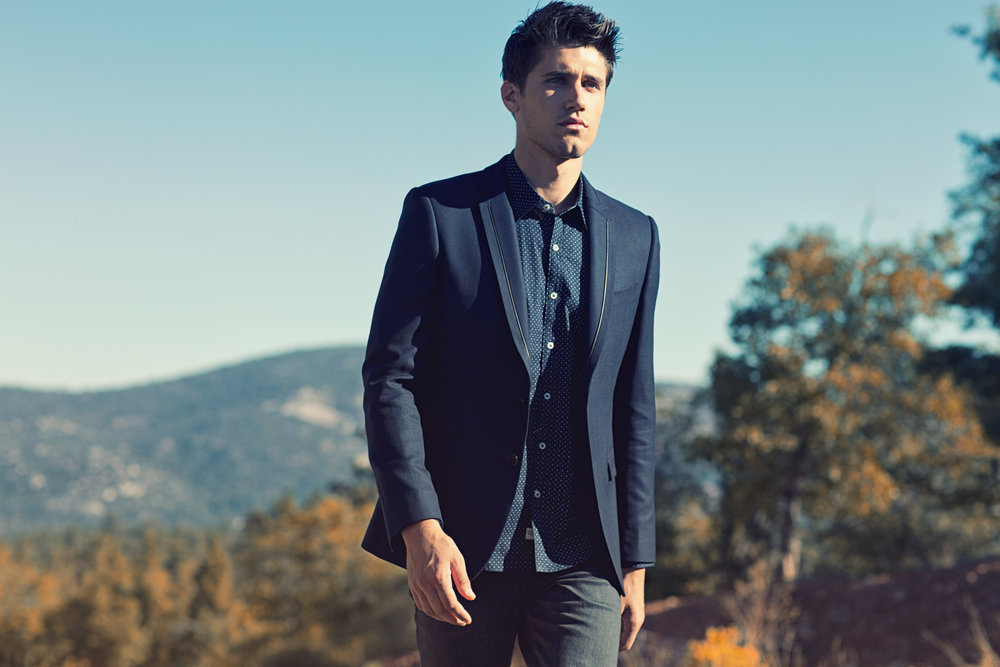 Mark DeLong - Lifestyle Photography - Man walking in a blue blazer with a mountain view in the background