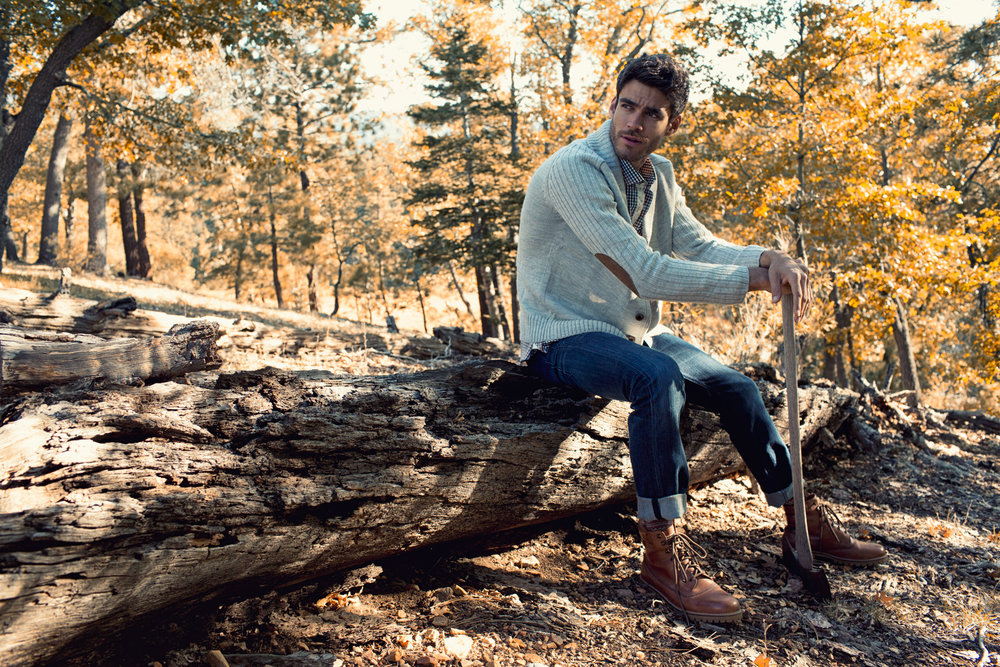 Mark DeLong - Lifestyle Photography - Man sitting on a log holding an axe in a cream sweater