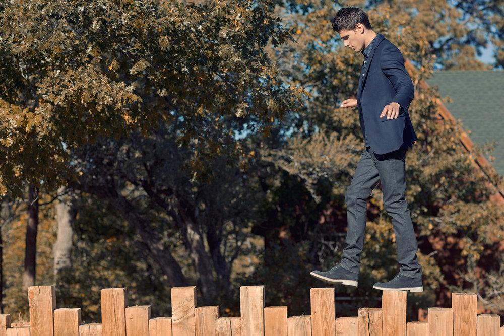 Mark DeLong - Lifestyle Photography - A man walking along a fence post wearing a blue blazer