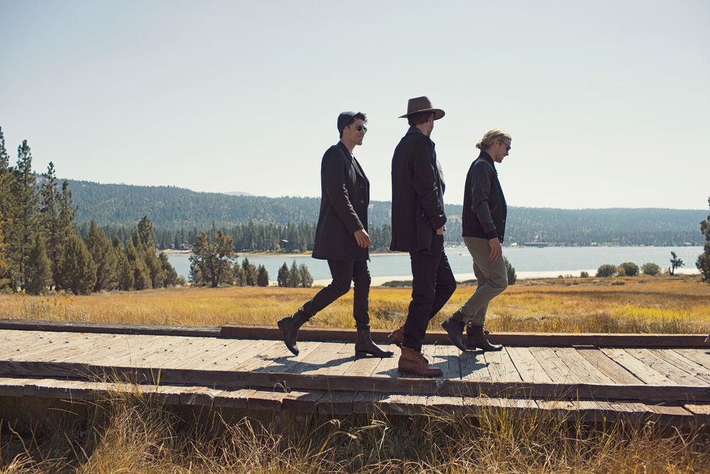 Mark DeLong - Lifestyle Photography - A group of men walking on a wooden dock in fall with a lake in the background