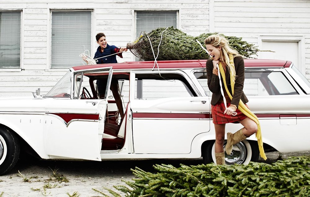 Mark DeLong - Lifestyle Photography - Two girls tying a Christmas tree to the top of a retro car