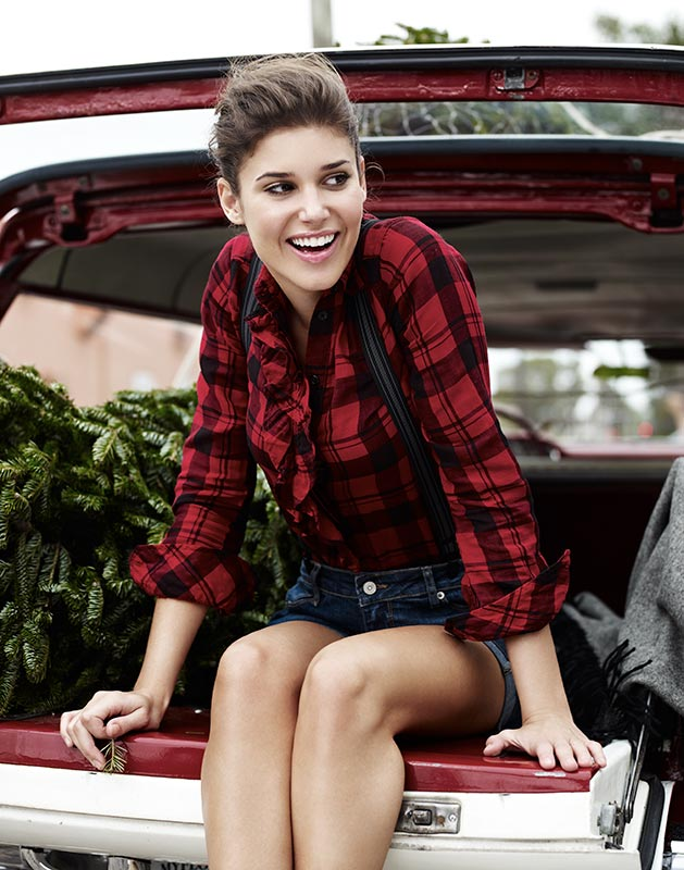 Mark DeLong - Lifestyle Photography - A woman in a plaid shirt sitting in the trunk of a retro car by a Christmas tree