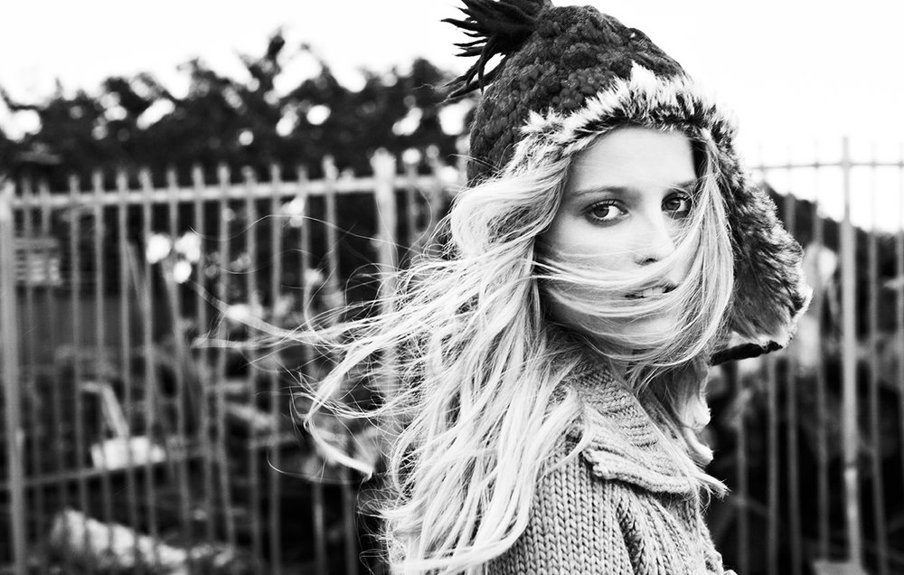 Mark DeLong - Lifestyle Photography - A blonde model in a winter hat walking in front of a fence with the wind blowing in her hair