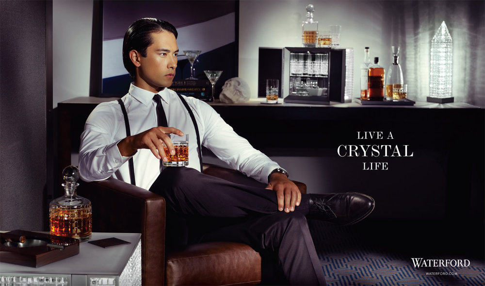 Mark DeLong - Commercial Photography - Man in dress clothes and suspender sits with a bottle of liquor.