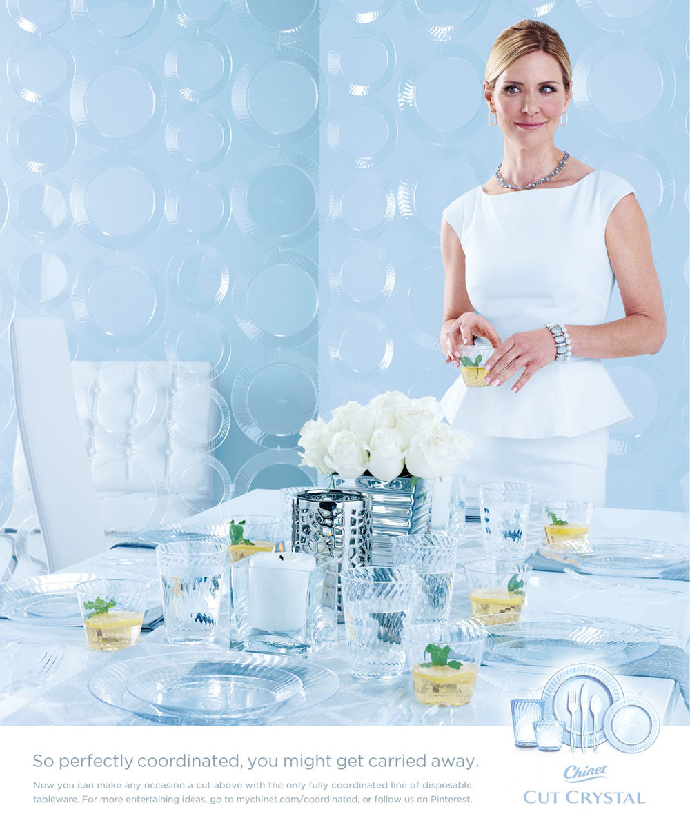 Mark DeLong - Commercial Photography - Woman in all white room wearing all white in front of a table.