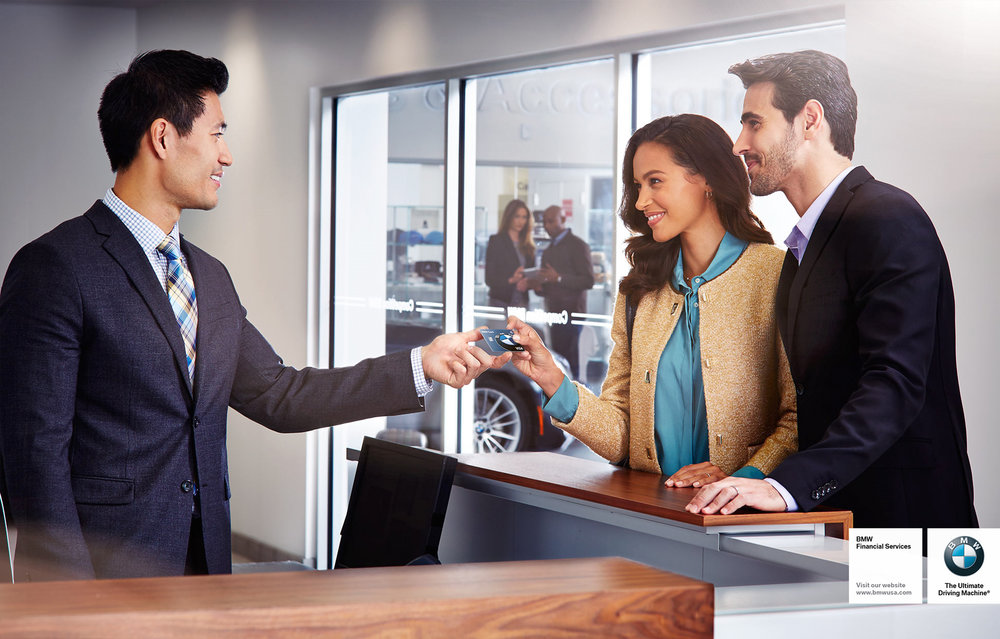Mark DeLong - Commercial Photography - Couple handing a car sales man a card with a BMW symbol on it.