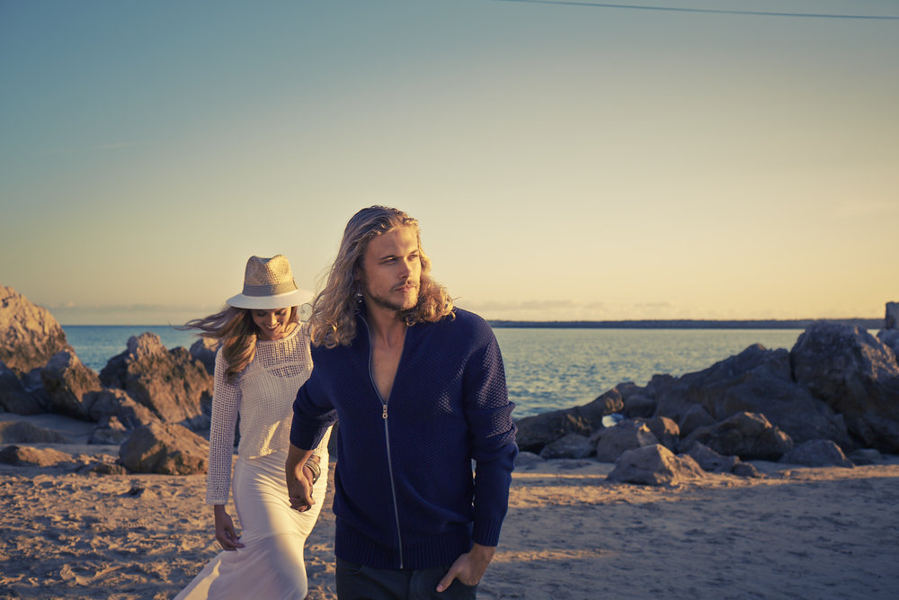 Mark DeLong - Lifestyle Photography - Man in a sweatshirt holding hands with a woman in a white dress and sun hat on the beach at sunset