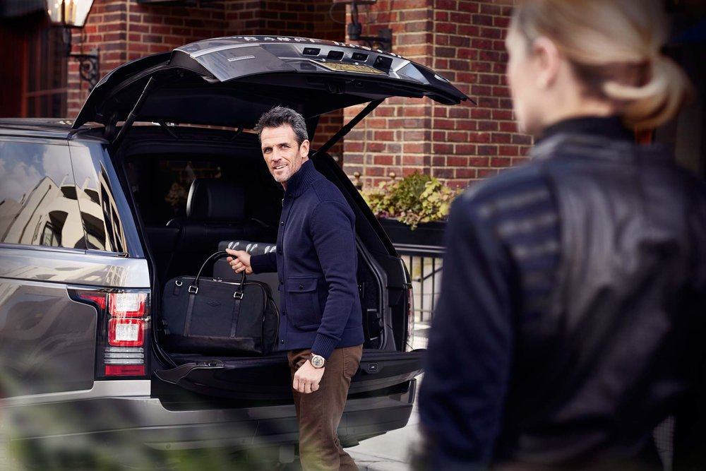 Mark DeLong - Commercial Photography - Man looking at wife as he lifts a bag out of the trunk of their SUV.