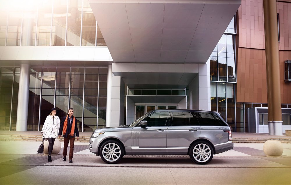 Mark DeLong - Commercial Photography - Couple walking towards a silver SUV parked in front of a hotel.