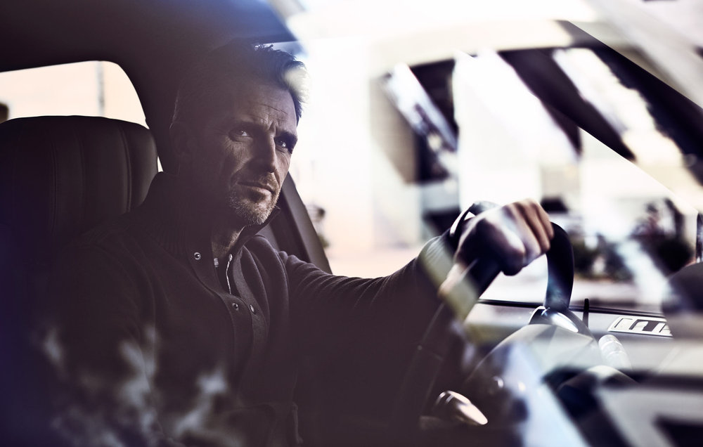 Mark DeLong - Commercial Photography - Up close view of a man driving a SUV.