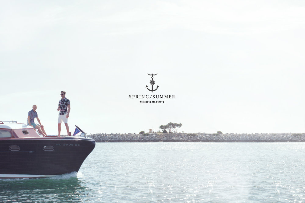 Mark DeLong - Lifestyle Photography - Two men standing and sitting on a cris craft boat moving across a lake
