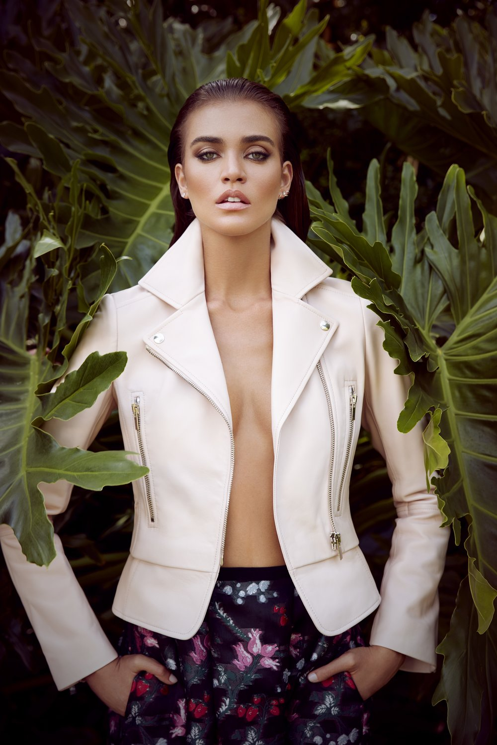 Tan brunette woman wearing open white leather jacket standing in front of large plant leaves - Mark DeLong: Fashion Gallery