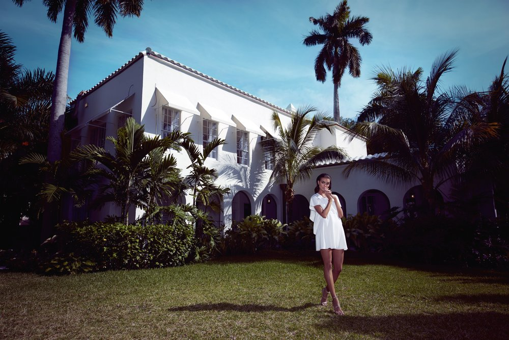 Tan brunette woman wearing white dress standing in grass in front of tropical white home with palm trees - Mark DeLong: Fashion Gallery