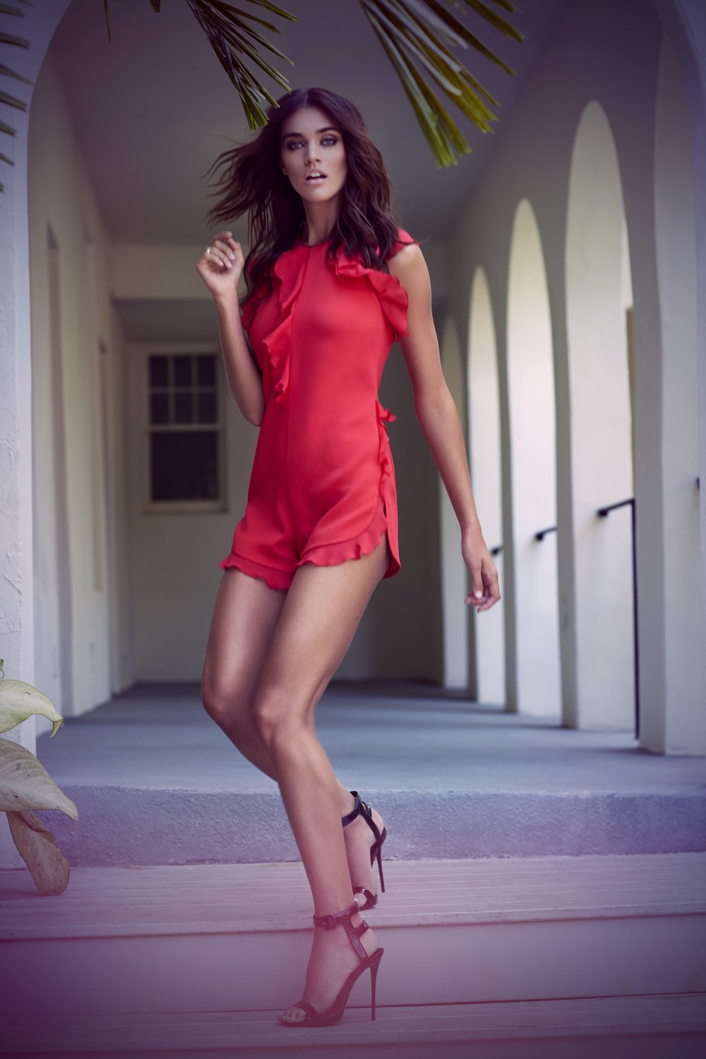 Tan brunette woman wearing red silk jumpsuit dress with black high heels walking down steps - Mark DeLong: Fashion Gallery